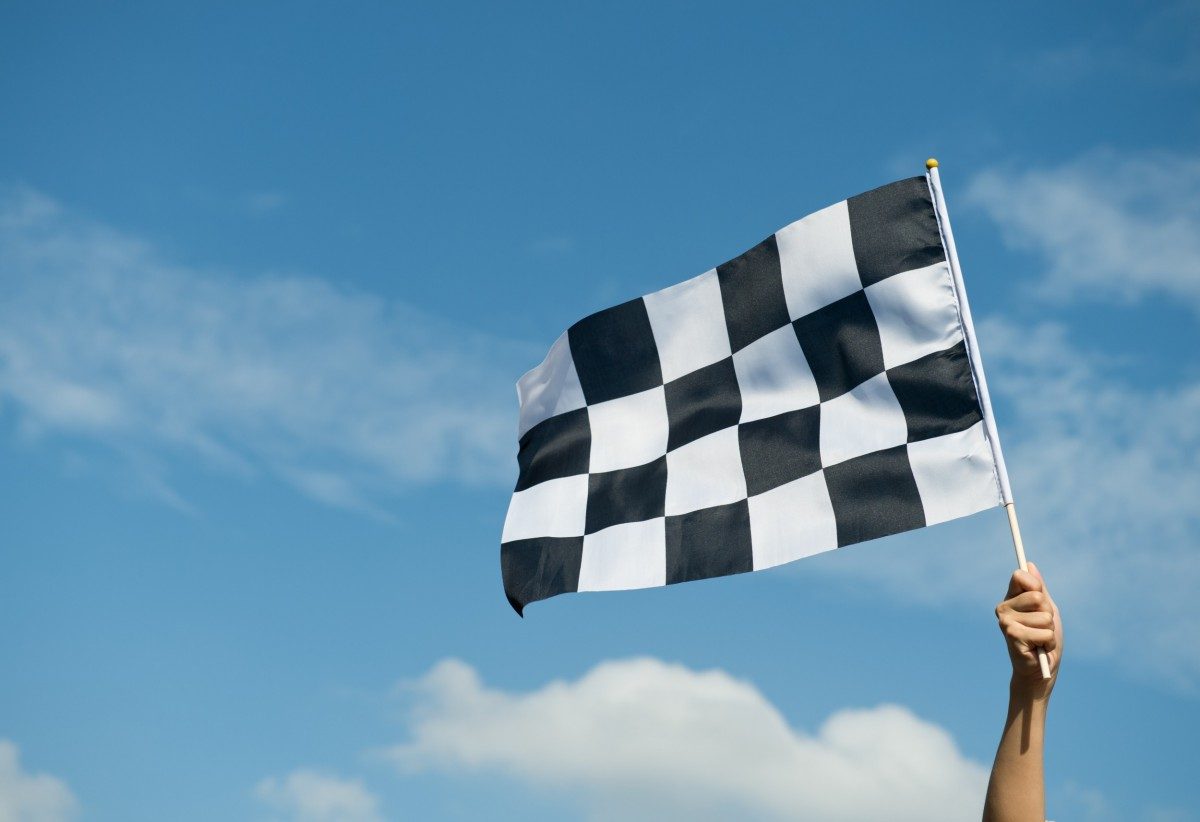 Hand holding a racing flag in the air